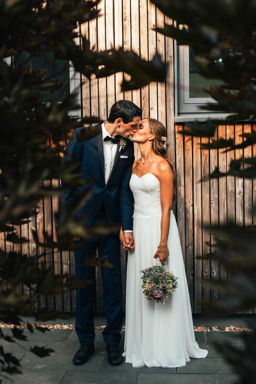 Küssendes Brautpaar bei Hochzeit im Hochsommer