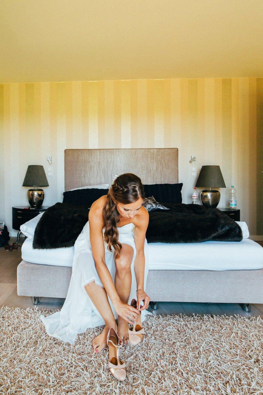 Sommerbraut beim getting ready auf dem Bett beim Stöckelschuhe anziehen