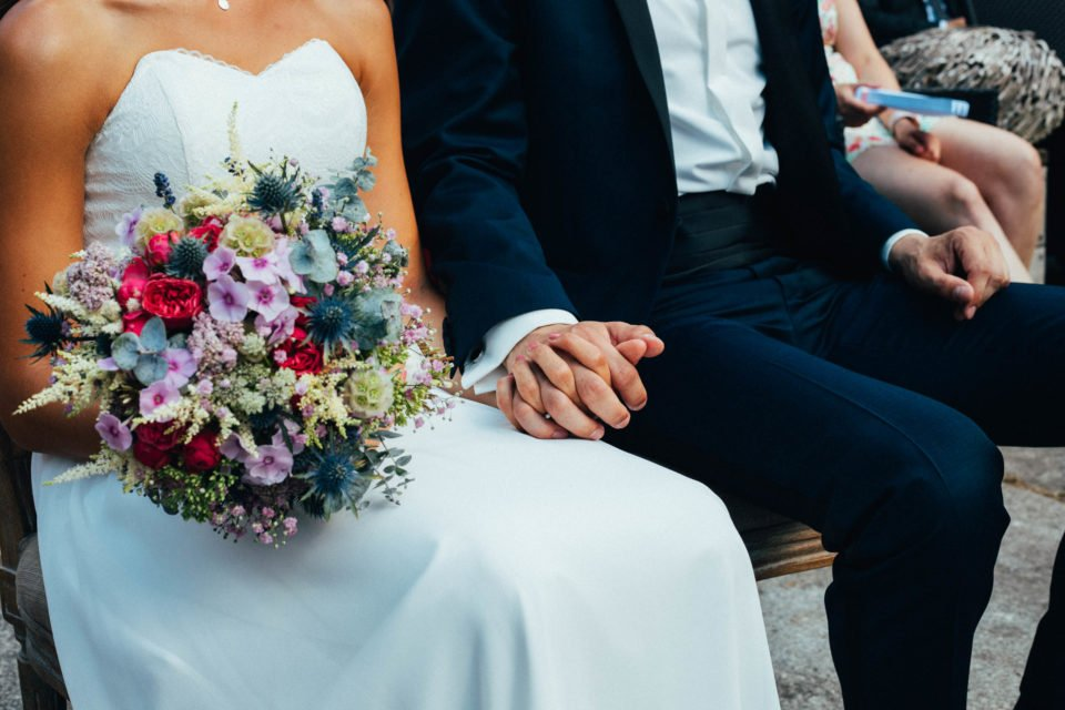 Braut mit Brautstrauß hält Hand des Bräutigams bei der Trauung