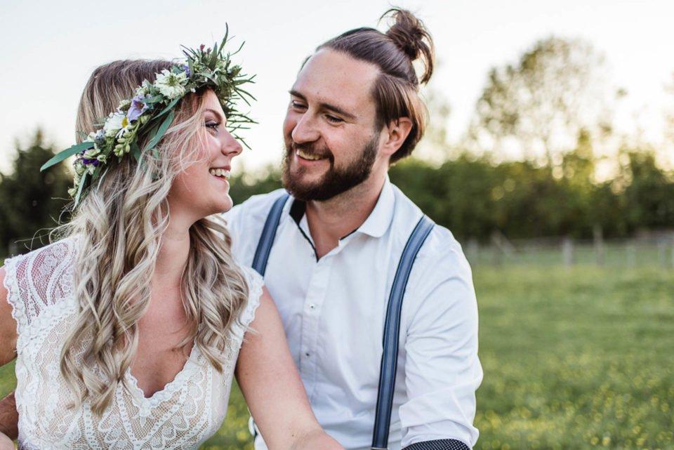 Boho Braut strahlt Bräutigam an