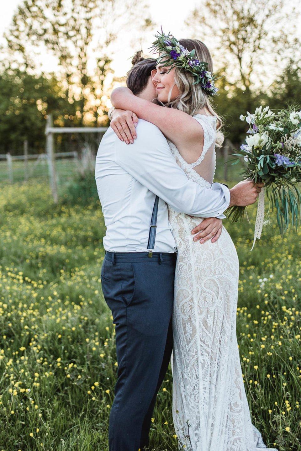 Boho Brautpaar umarmt sich auf der Wiese