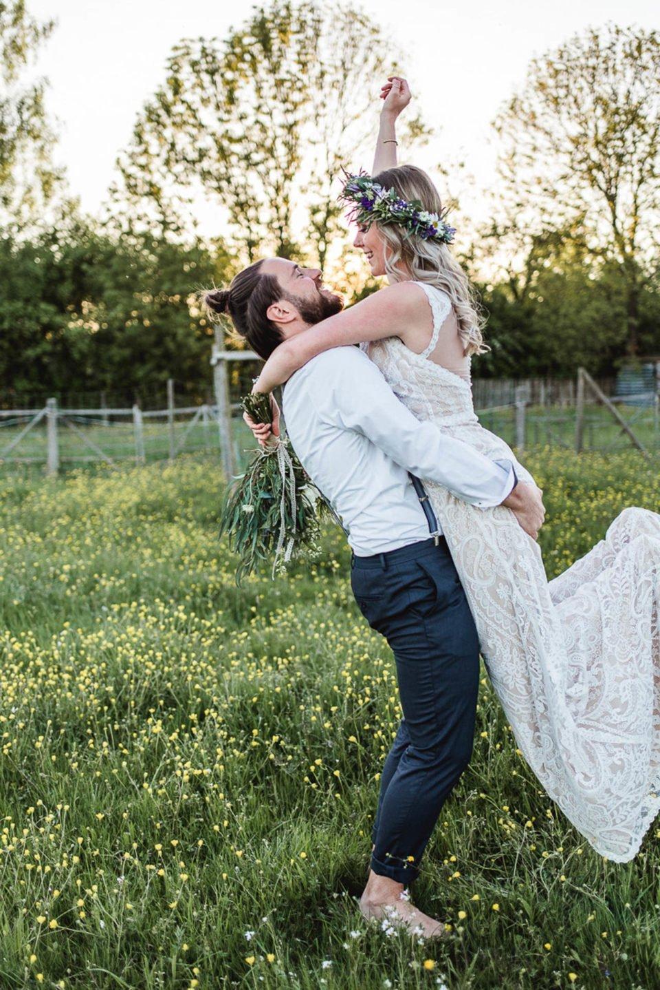 Bräutigam hält strahlende Braut nach oben