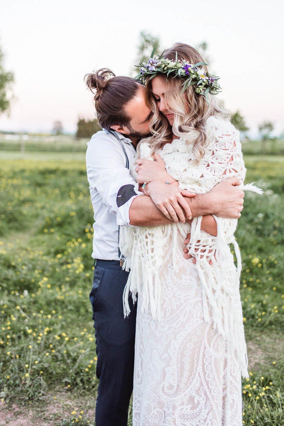 Bräutigam umarmt Boho Braut auf der Wiese