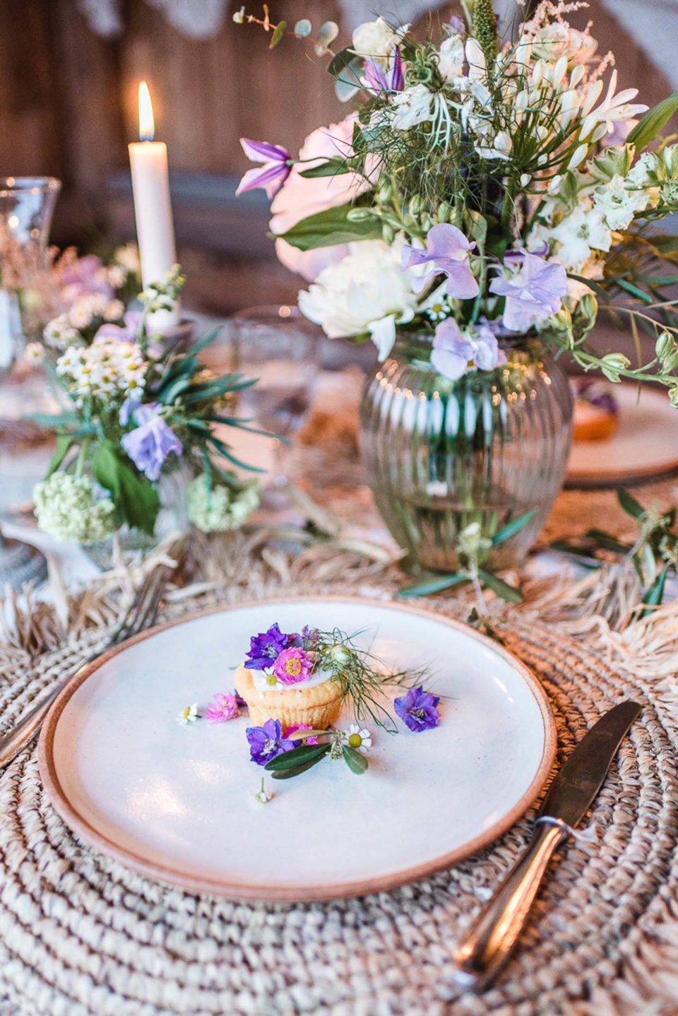Blumen und kleines Törtchen auf Paletten-Tisch