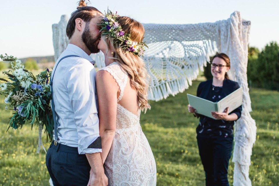 küssendes Brautpaar bei freier Trauung auf der Wiese