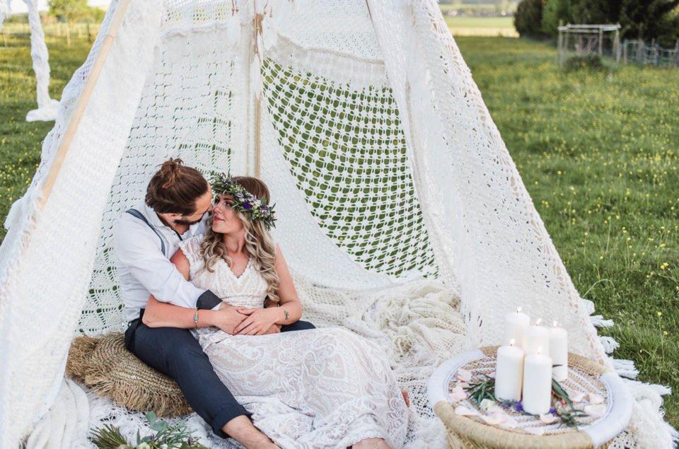 Boho Brautpaar sitzt im Tipi um himmelt sich an
