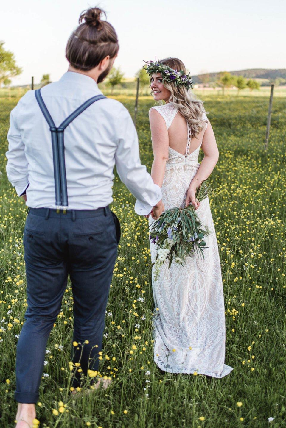 Boho Brautpaar auf der Wiese Hand in Hand