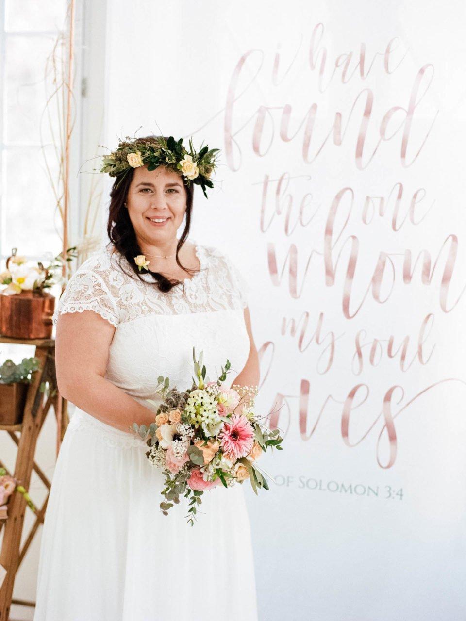 Plus Size Braut im Vintage Spitzenkleid mit Blumenkranz im Haar und Brautstrauß