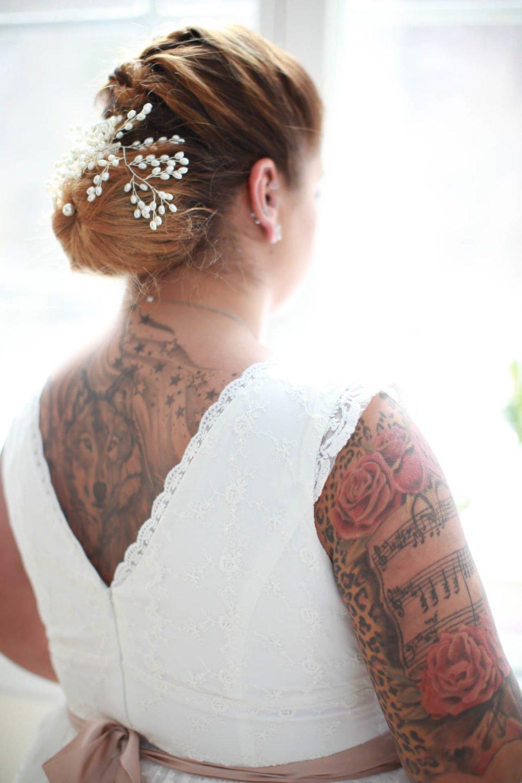 Haarschmuck an tätowierter Curvy Bride im Spitzenkleid