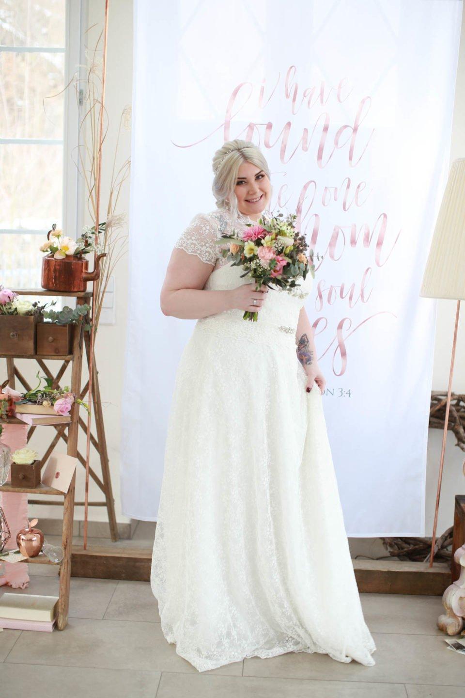 Glückliche Braut im Curvy Hochzeitskleid mit Spitze