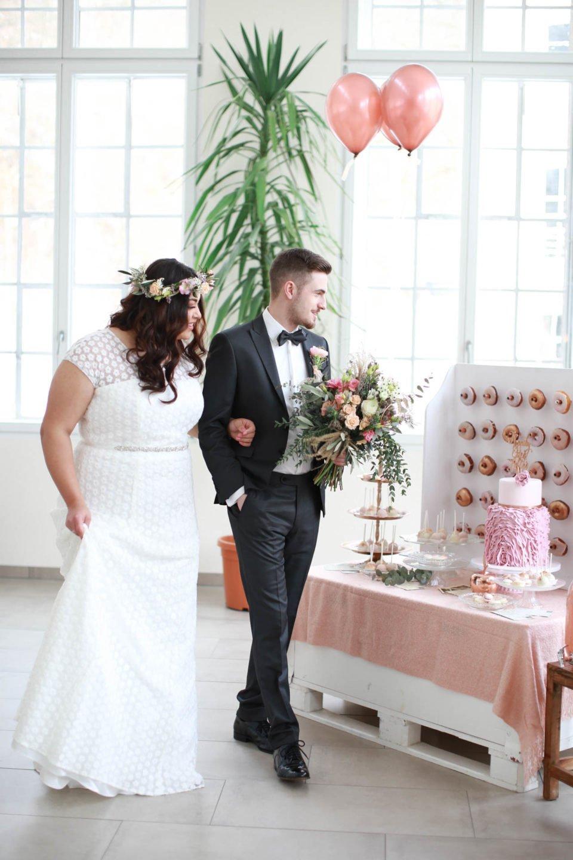 Curvy Braut mit Bräutigam vor Donat-Wand