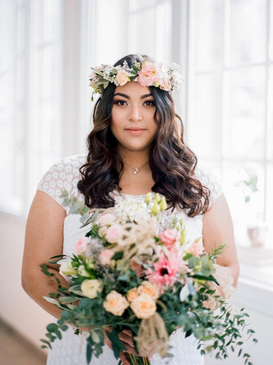 Curvy Braut mit Brautstrauss und Blumenkranz im Haar