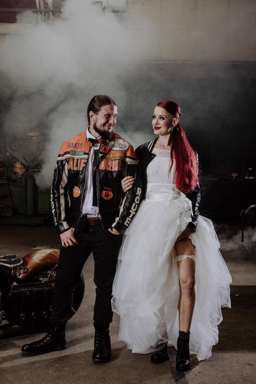 Biker Brautpaar strahlt sich glücklich an und Braut zeigt Strumpfband