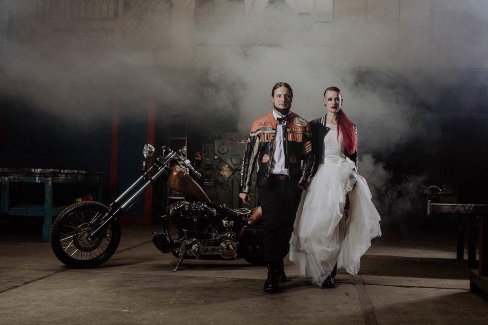 Biker Hochzeit - Brautpaar mit Harley im Hintergrund