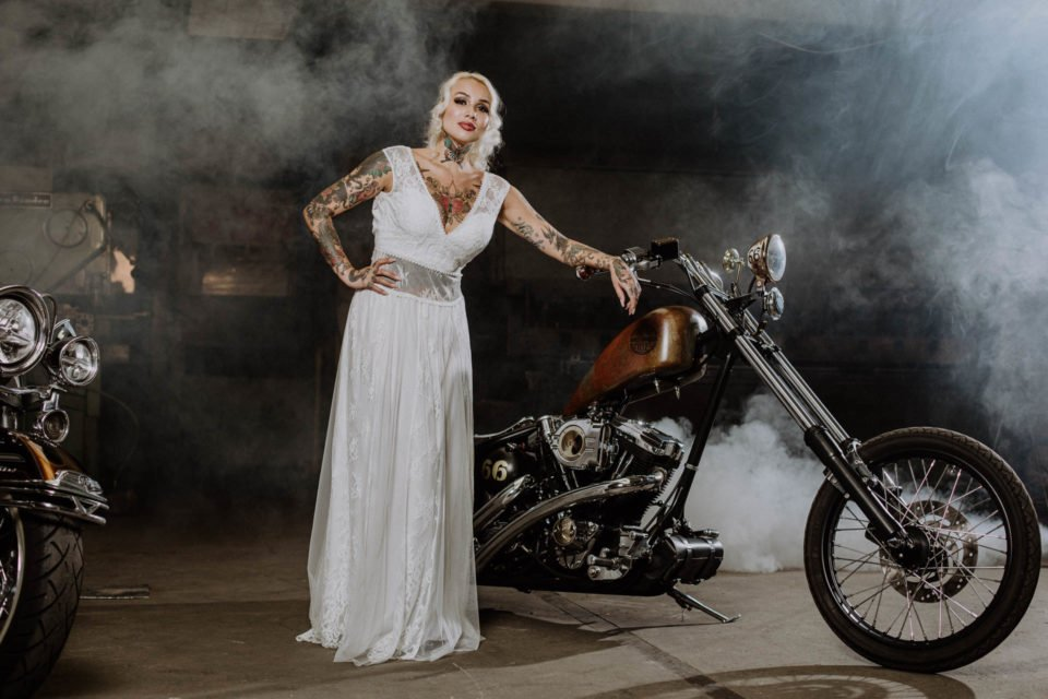 Motorrad Hochzeit - Rocker Braut im bauchfreien Brautkleid an Harley gelehnt