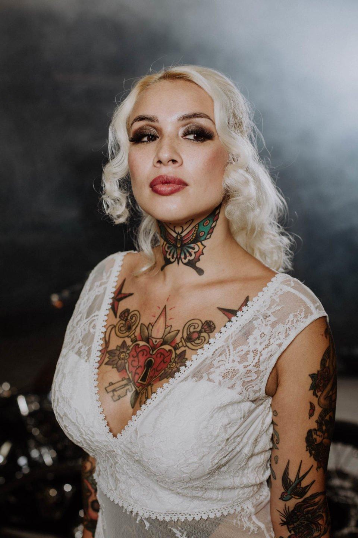 Blonde Braut im Brautkleid mit V-Ausschnitt mit tätowiertem Dekolleté