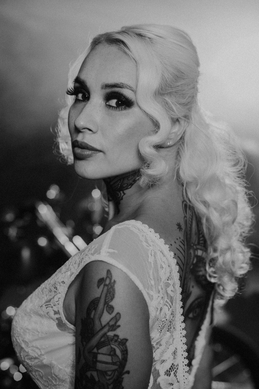 Blonde, tätowierte Braut im Brautkleid mit Spitze