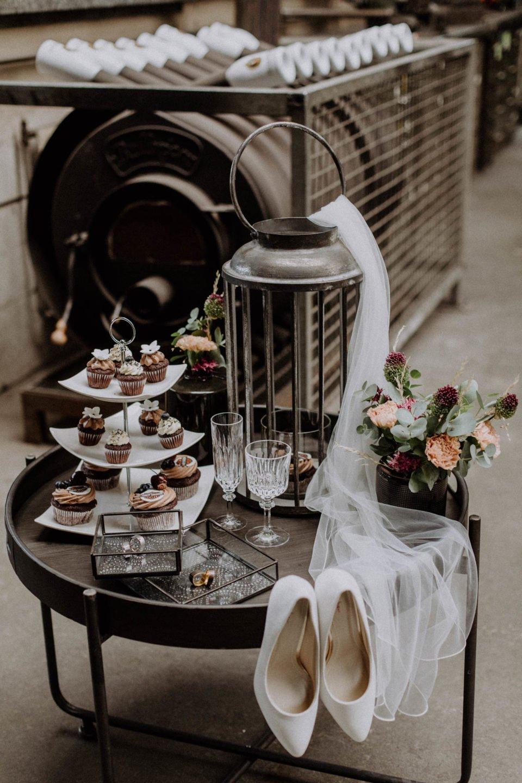 Beistelltisch mit Cup Cakes, Ringen, Brautstrauß und Schleier