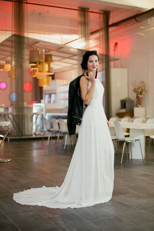 Braut mit schlichtem Brautkleid und Lederjacke über der Schulter