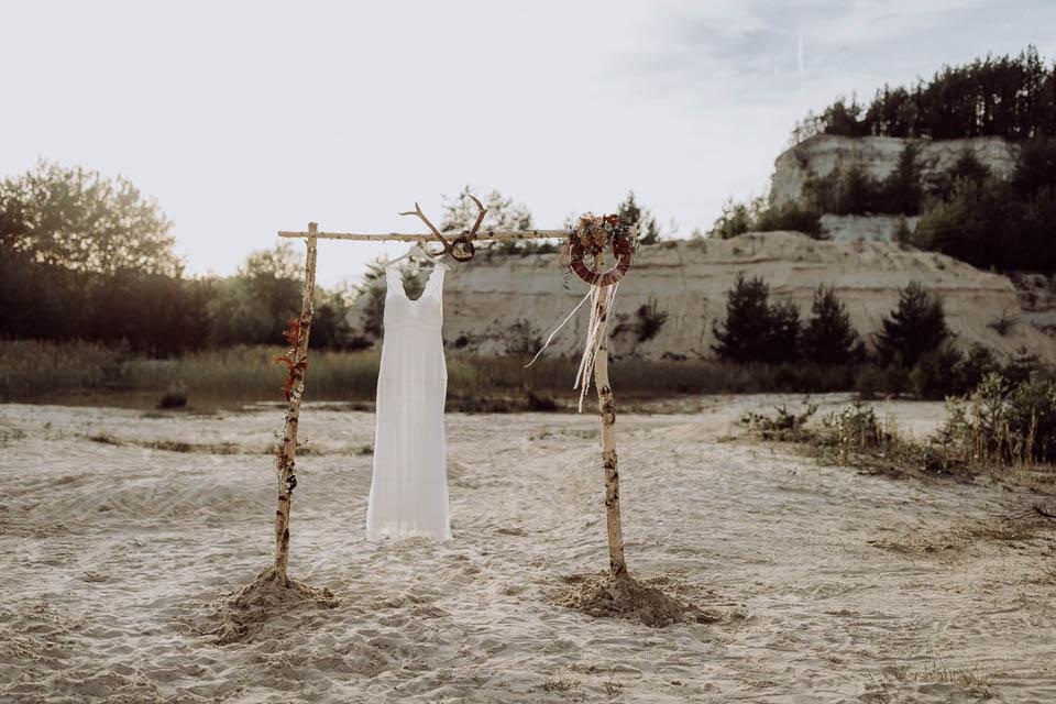 Boho Brautkleid hängt am Traubogen