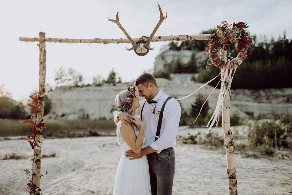 Boho Brautpaar unter Traubogen bei Elopement Hochzeit