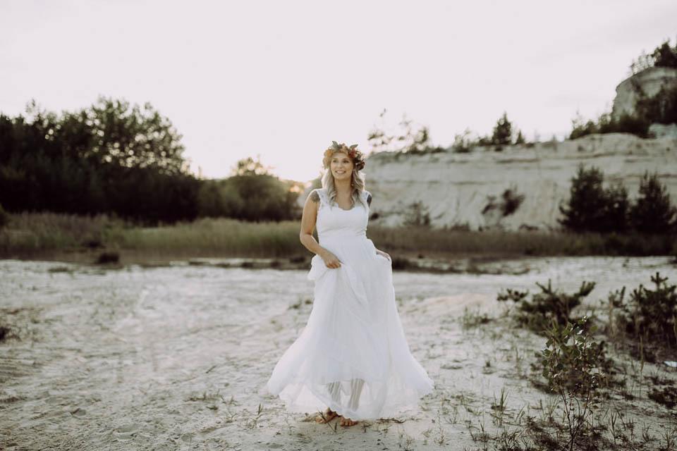 Glücklich strahlende Boho Braut barfuß im Sand