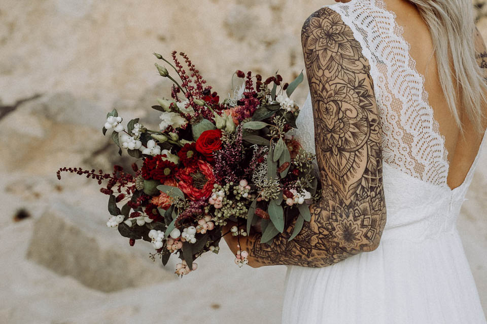 Tätowierte Braut hält Brautstrauß mit voll tätowiertem linken Arm