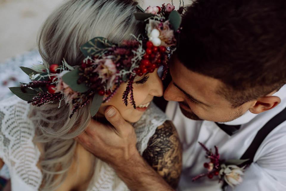 Boho Braut lächelt Bräutigam nach Kuß an