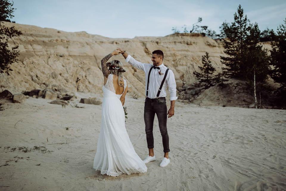 Tanzendes Boho Brautpaar im Sand