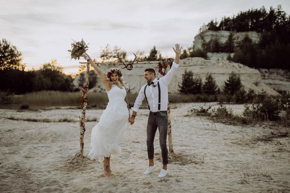 Elopement Hochzeit - Brautpaar springt vor dem Traubogen glücklich in die Luft