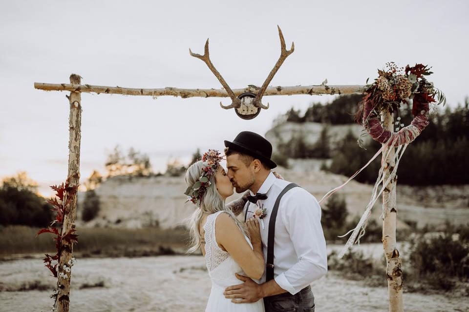 Boho Brautpaar küsst sich unter dem Traubogen