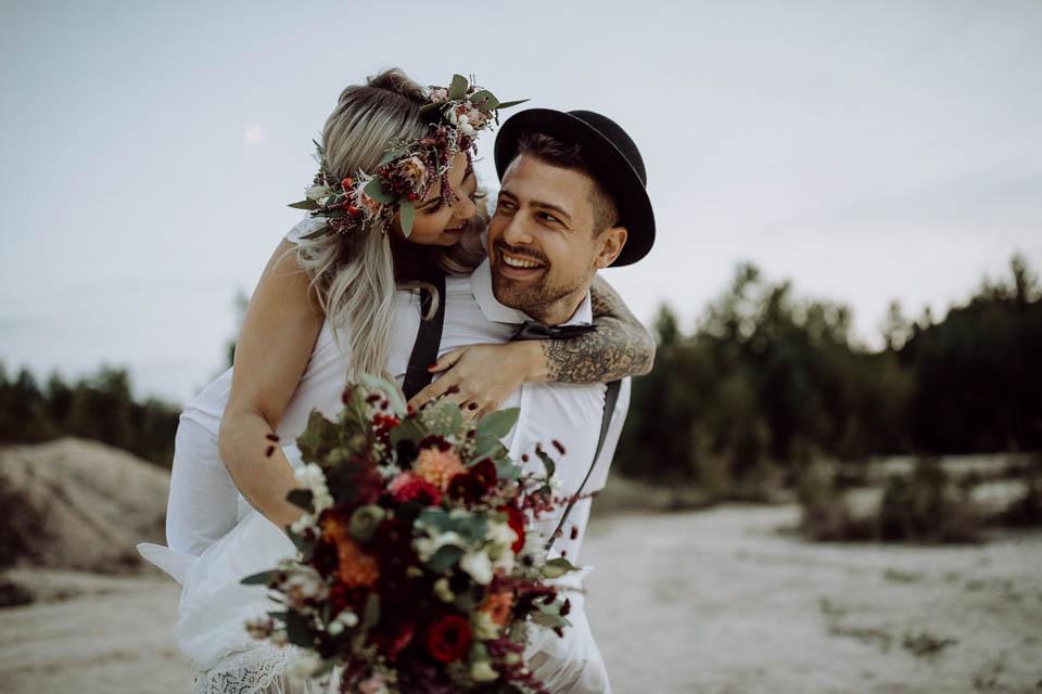 Bräutigam trägt Boho Braut Huckepack