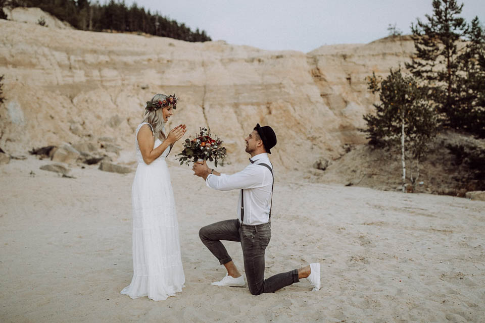 Bräutigam macht Braut Antrag im Sand
