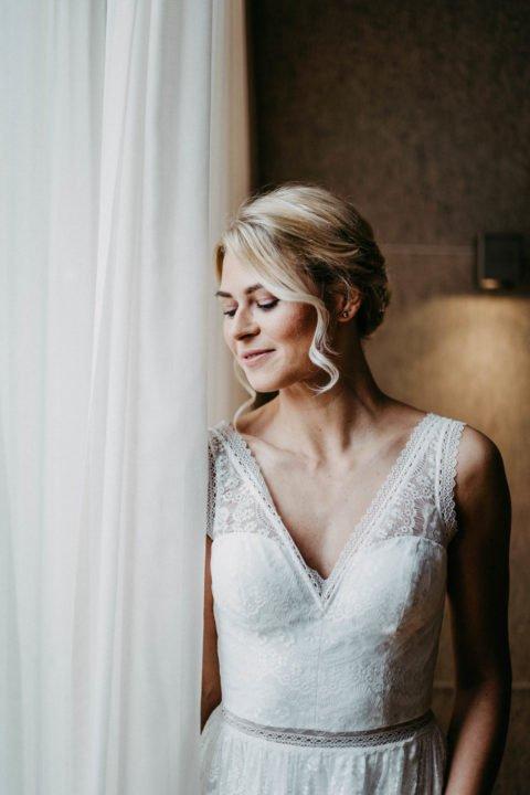 Brautkleid mit Spitzenträgern an blonder Braut