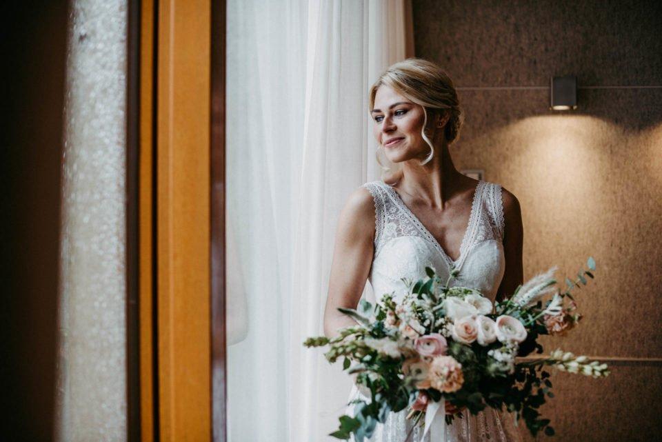 Strahlend blonde Braut im Spitzenkleid mit ausladendem Brautbouquet