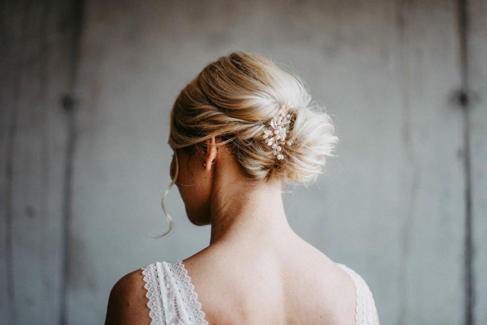 blonde Braut mit Steckfrisur und Haarschmuck von hinten