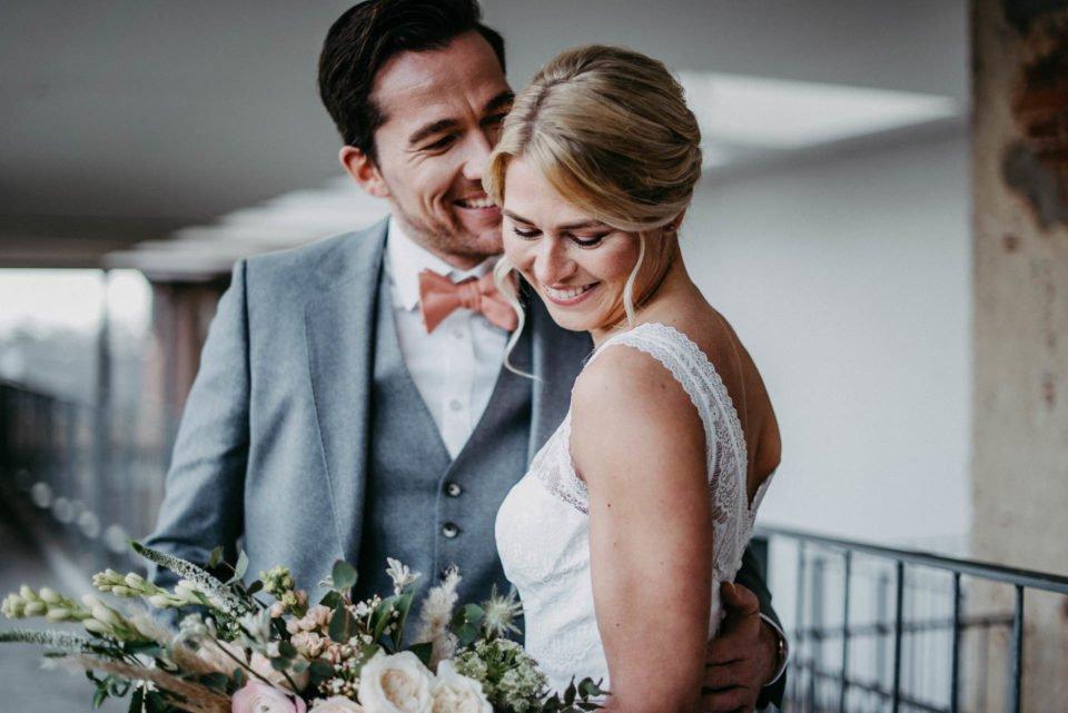 lächelndes Brautpaar umarmt sich