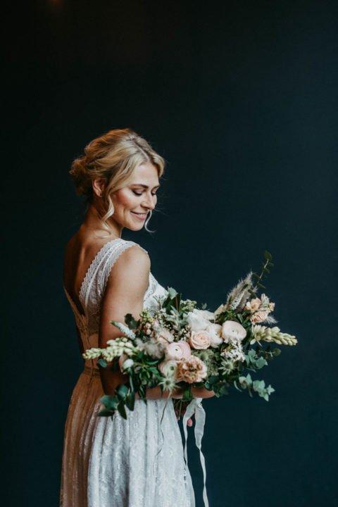 lächelnde Braut von hinten mit Brautstrauß