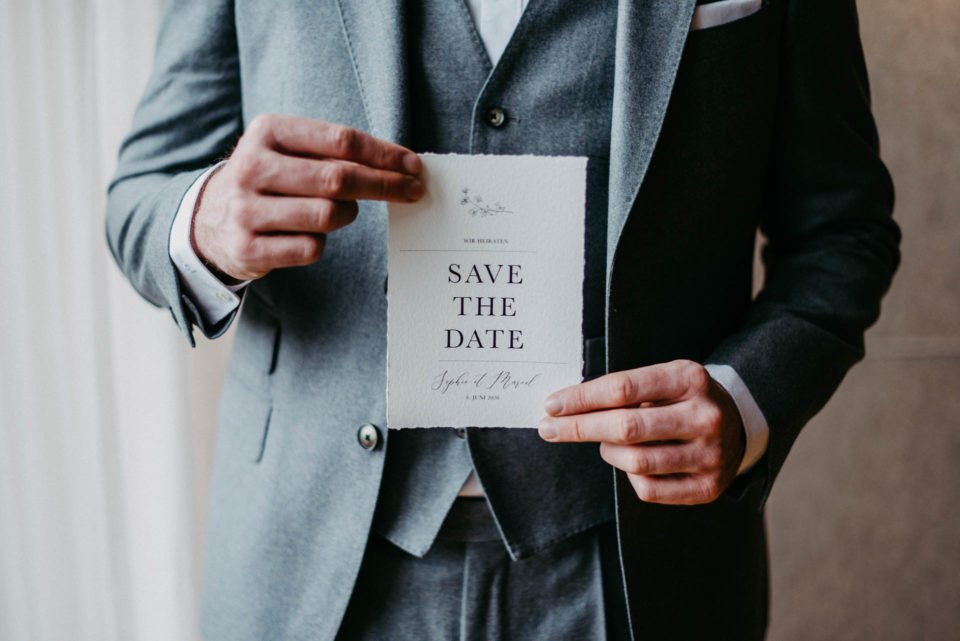 Bräutigam hält Save the Date Karte