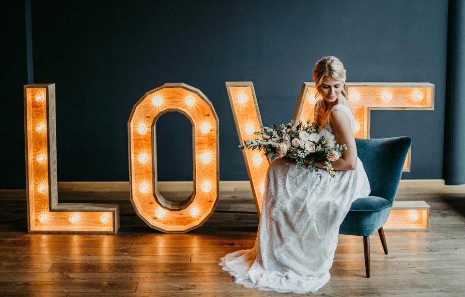 Braut sitzt vor leuchtenden LOVE Großbuchstaben aus Holz