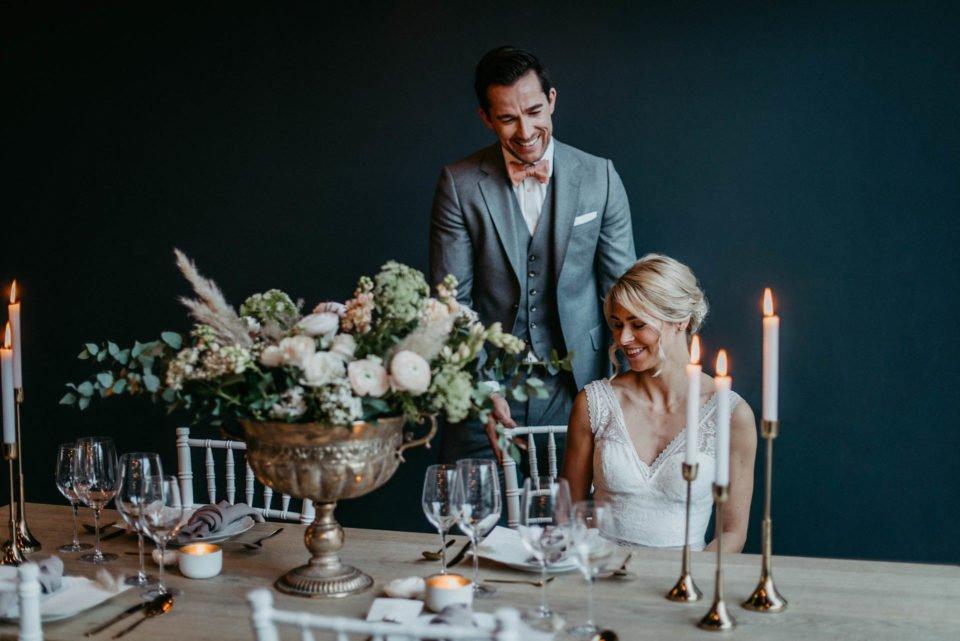 Brautpaar lächelt am Tisch der modernen Hochzeitsinspiration