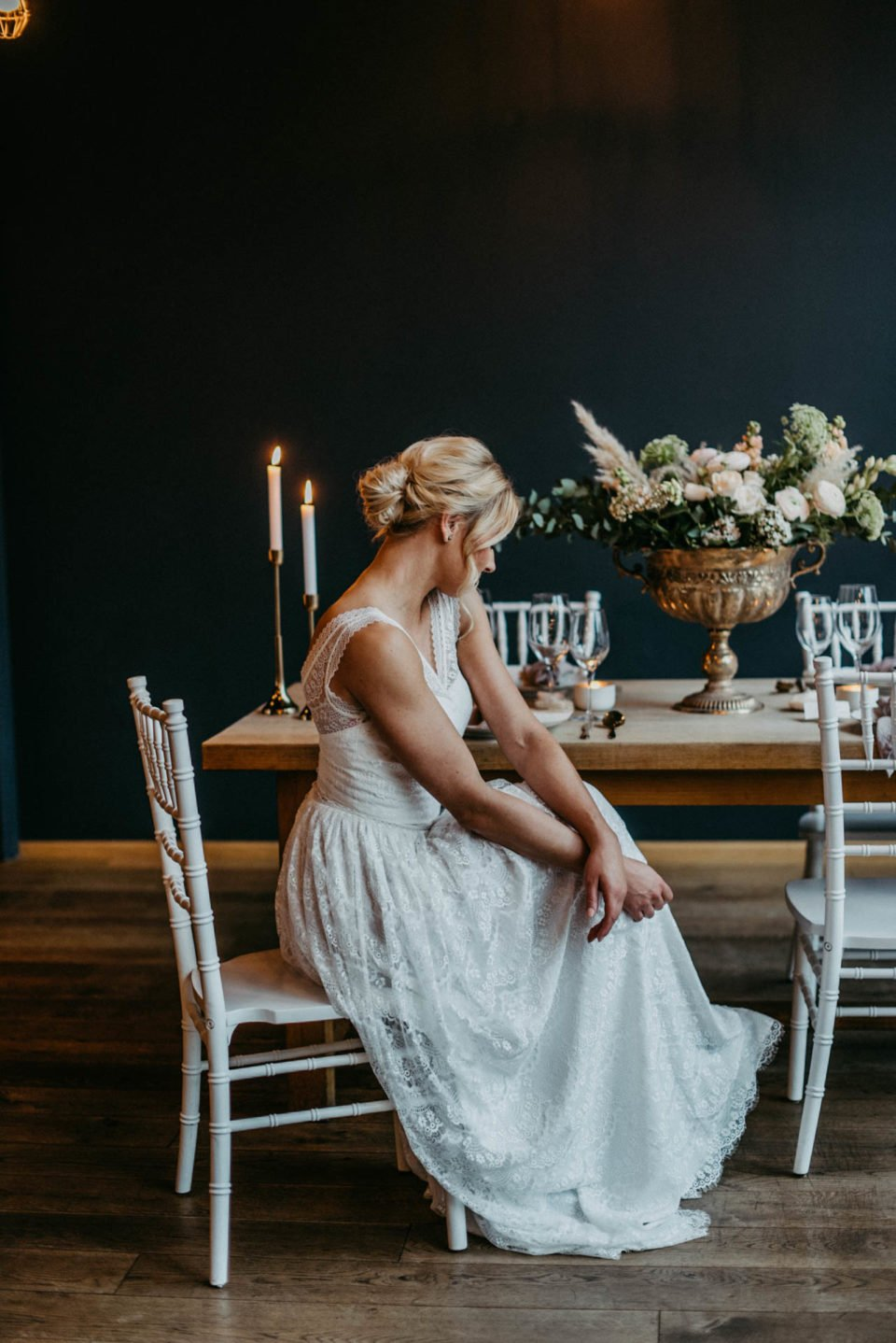 Braut sitzt im Spitzenkleid am Hochzeitstisch