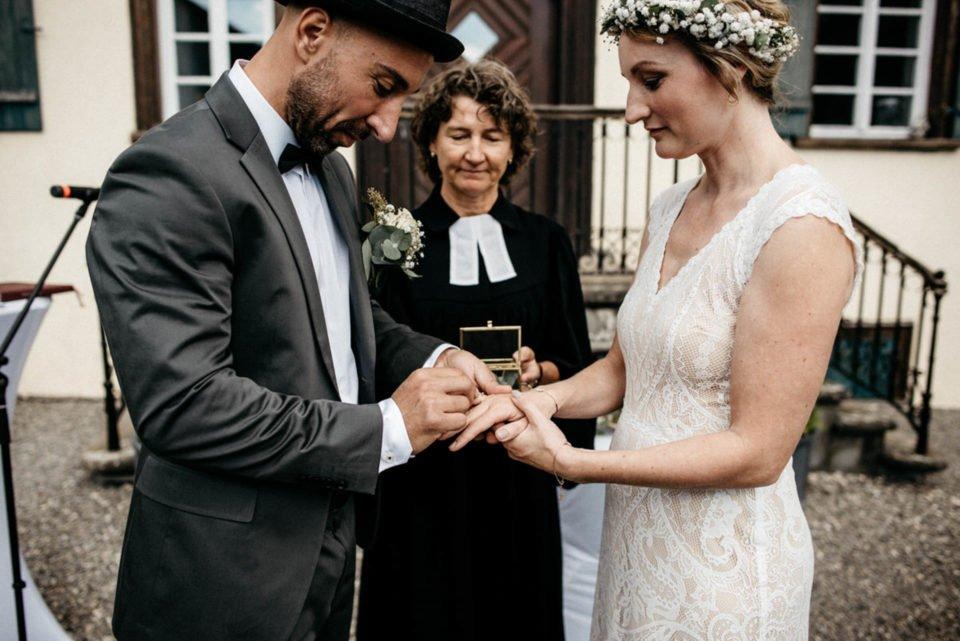Bräutigam steckt Braut Ehering an