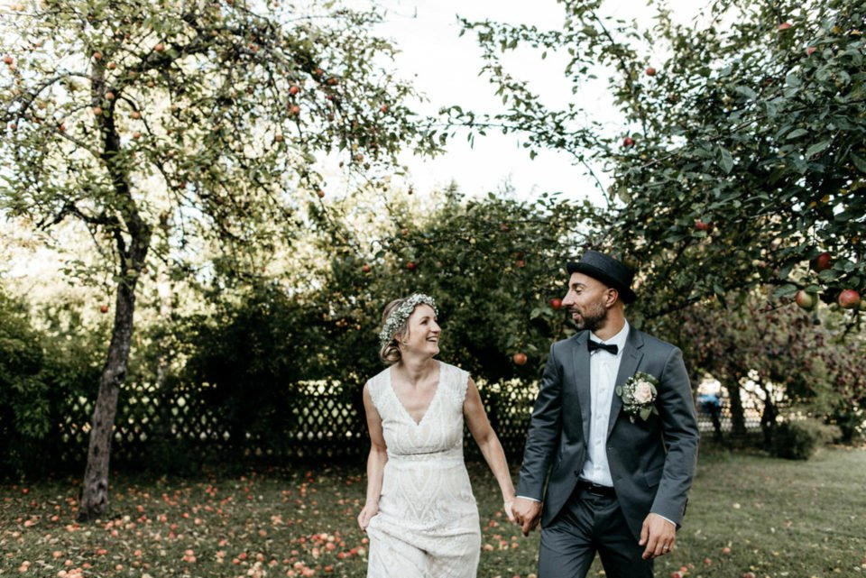 September Hochzeit, Brautpaar Hand in Hand neben Apfelbäumen