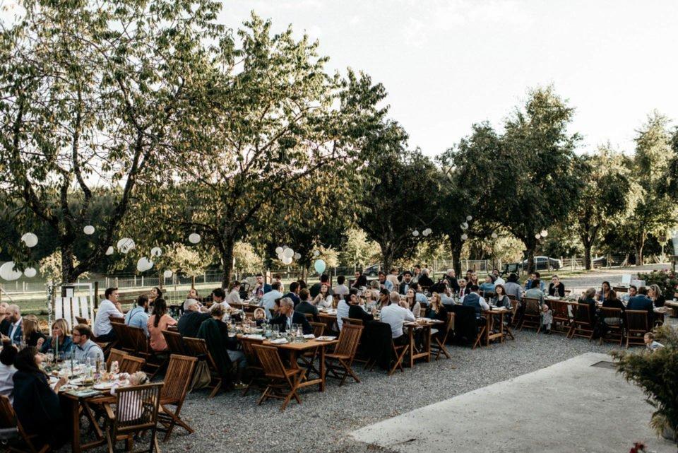 Hochzeitsgesellschaft sitzt im Freien bei September Hochzeit
