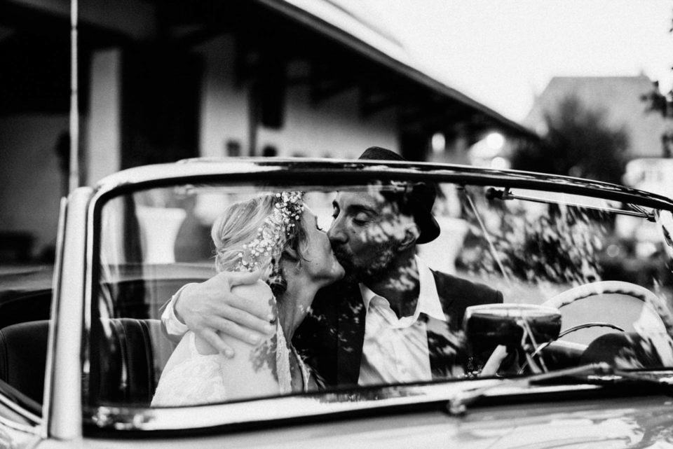 Brautpaar küsst sich im Hochzeitsauto