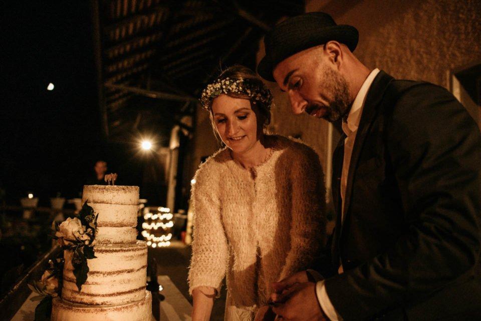 Brautpaar vor dreistöckiger Hochzeitstorte