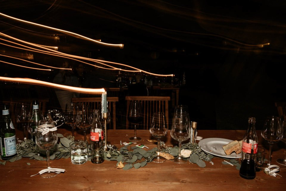 Tisch nach Hochzeitsfeier mit leeren Flaschen und Gläsern