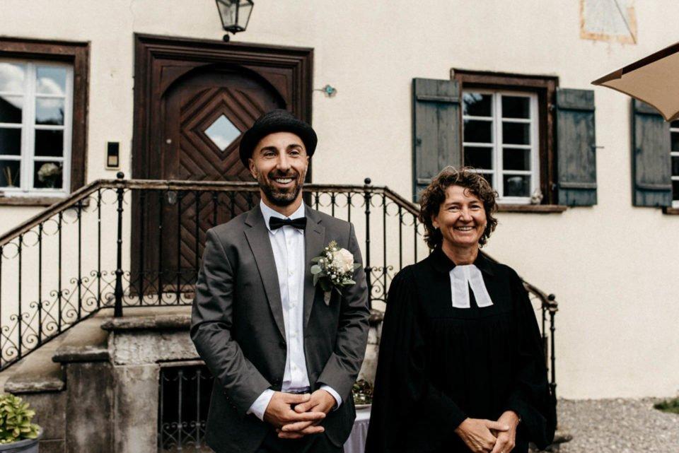 Bräutigam wartet neben Pfarrerin auf seine Braut für die Hochzeit im September