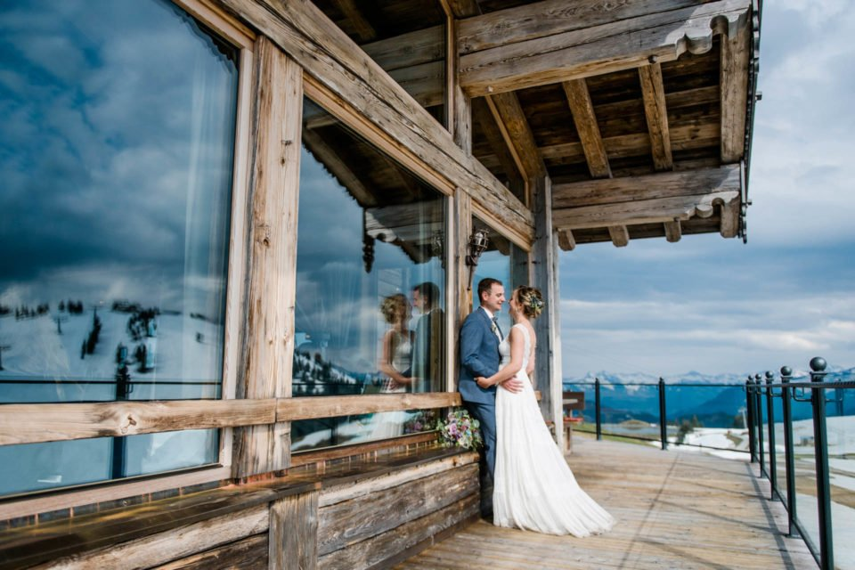 Maihochzeit auf der Tanzbodenalm, Brautpaar steht vor dem Almfenster